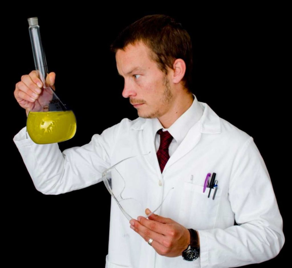 Lab Scientist holding a yellow liquid